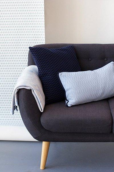 Interiørfoto af tapet og sofa med designet plaid og pyntepude