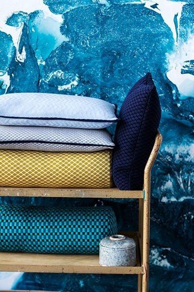 interiørfoto af blålig tapet og vogn med tekstildesignet pyntepuder