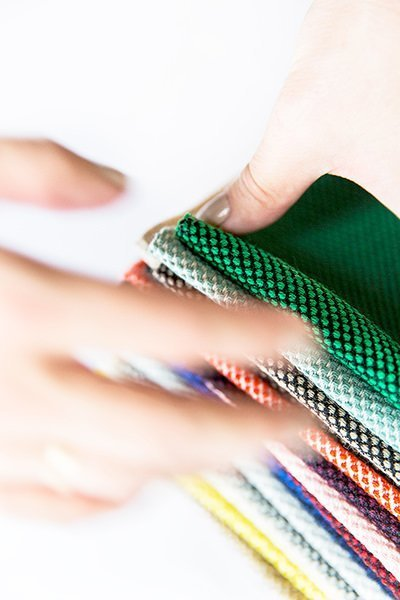 Foto af hænder der rækker ud efter prøver på tekstildesign