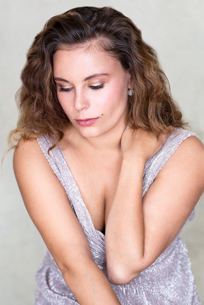 Portræt af glamourøse langhåret ung kvinde i lysegrå kjole